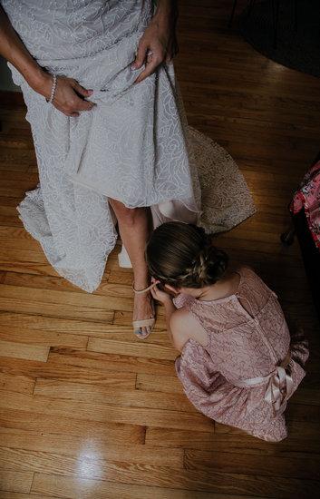 Junior bridesmaid helping bride with shoes