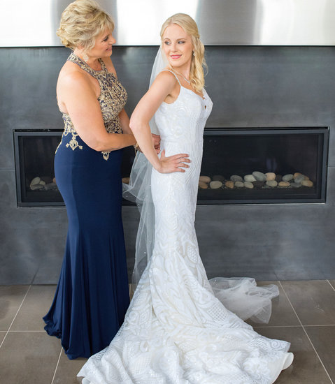 Bride's mom zips up her Blush West dress