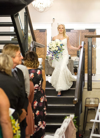 Bride walks down stairs in blue heels