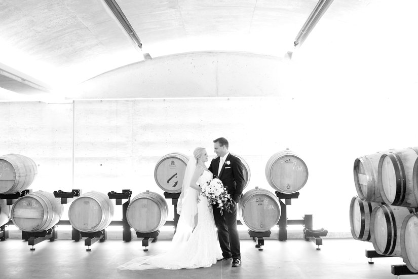 Bride & Groom in wine barrel cellar
