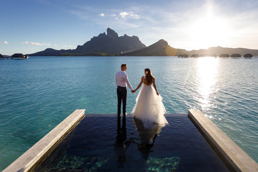 Bride and groom about to jump from their bungalow at the Four Seasons Resort Bora Bora