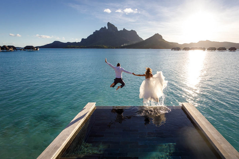 Bride and groom trashing the dress jumping from their bungalow at the Four Seasons Resort Bora Bora