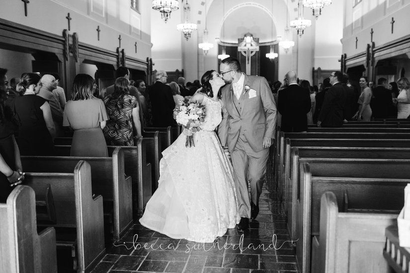 Bride and groom kiss while walking down aisle