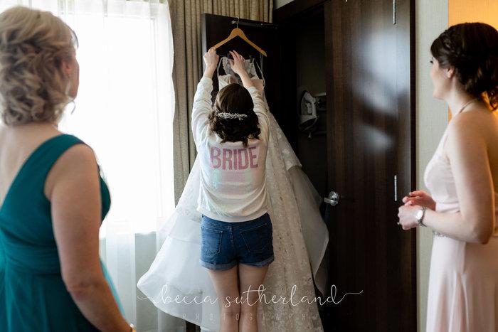 Bride takes dress off hanger